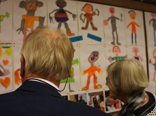 opa en oma kijken naar de werkjes van hun kleinkind